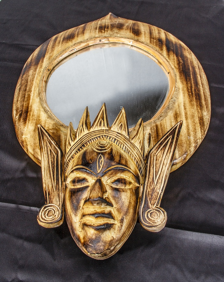 A mirror adorned with a decorative frame featuring a 'Mukha'
